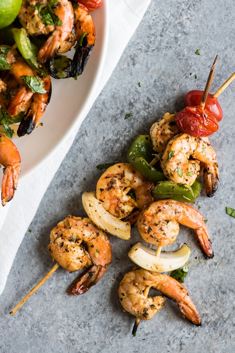 Two skewers of grilled shrimp with tomatoes, onions and bell peppers.