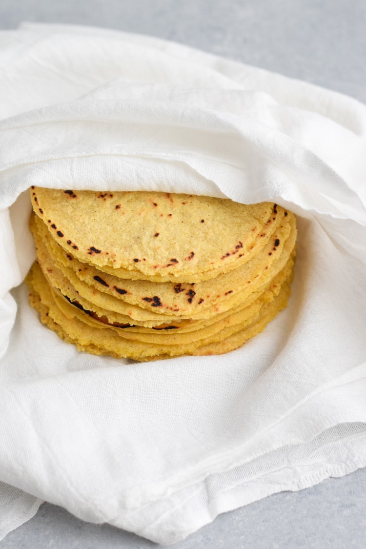 Cooked corn tortillas stacked on top of each other and wrapped in a white kitchen towel