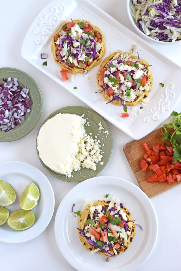 An overhead view of a Mexican feast featuring sopes topped with shredded chicken ground beef, and other ingredients like queso fresco, limes, and chopped tomatoes.