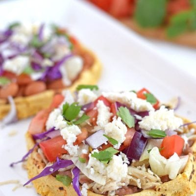 Mexican sopes recipe topped with refried beans, shredded chicken and queso fresco.