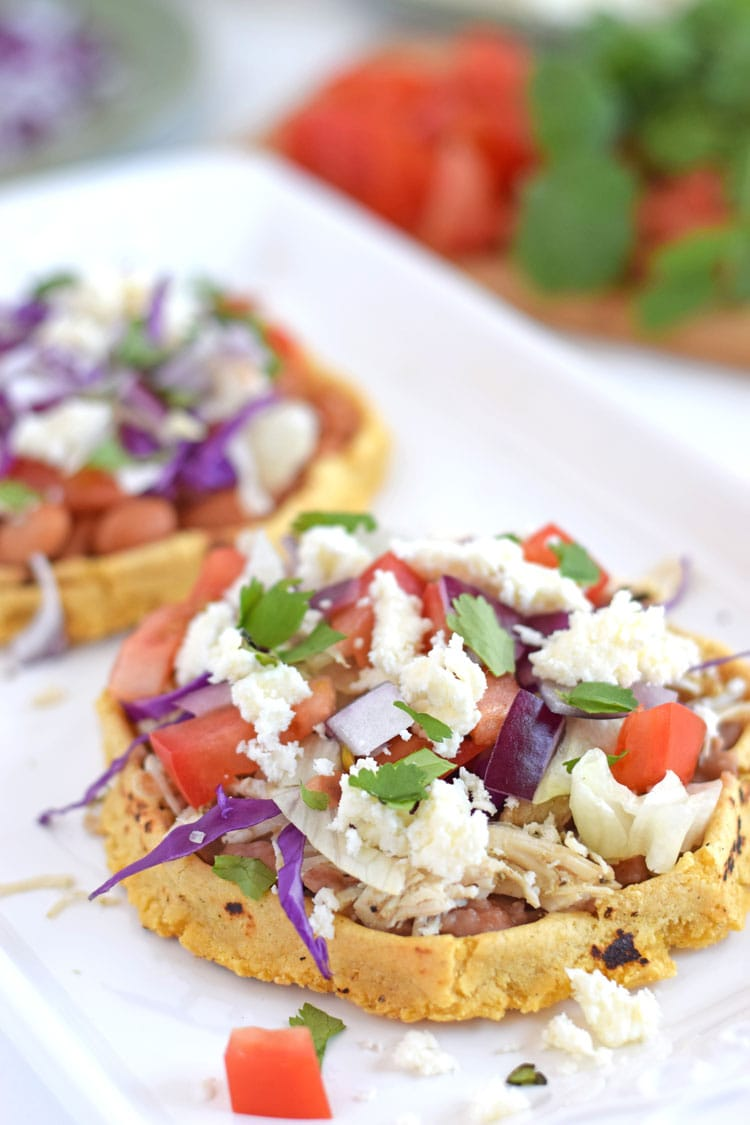 Mexican sopes recipe topped with refried beans, shredded chicken, queso fresco and veggies.