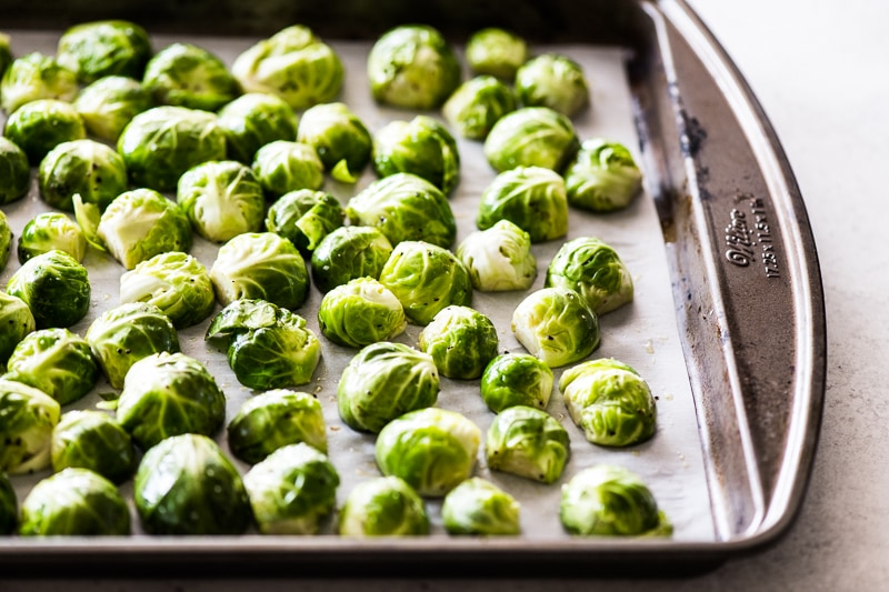 Raw and seasoned brussels sprouts on a pan
