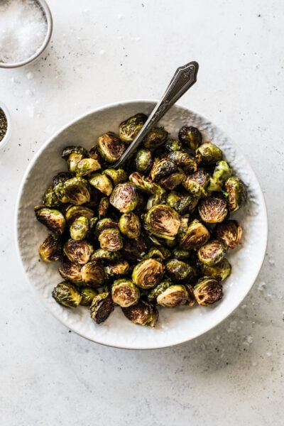 Honey Balsamic Brussel Sprouts in a white bowl topped with sea salt.