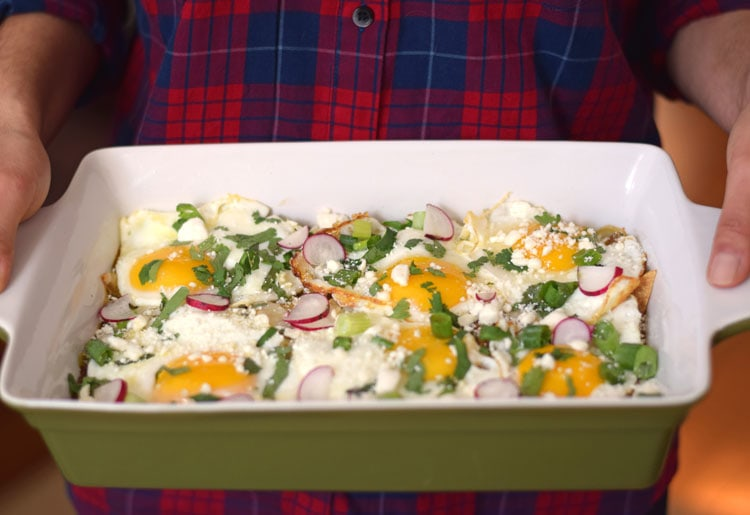 Made with baked corn tortillas covered in salsa verde and topped with sunny side-up eggs, fresh cilantro, radishes and green onions, this Mexican Salsa Verde Chilaquiles Casserole is the perfect breakfast and brunch dish. It's also gluten free and vegetarian, woo woo! // isabeleats.com