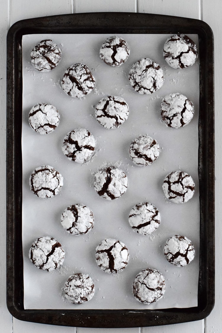 A sheet pan full of chocolate crinkle cookies.
