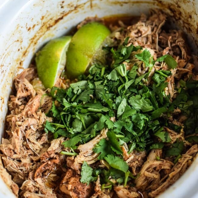 Chicken Carnitas in a slow cooker topped with cilantro.