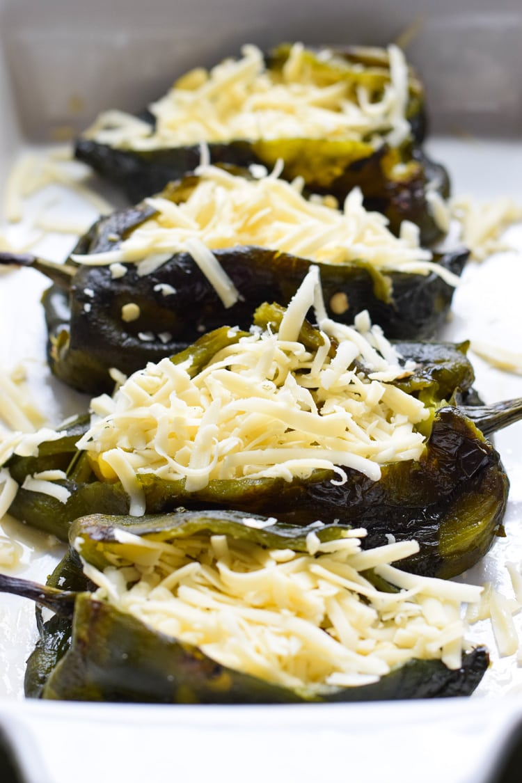 Roasted poblanos stuffed with shredded cheese in a baking dish.