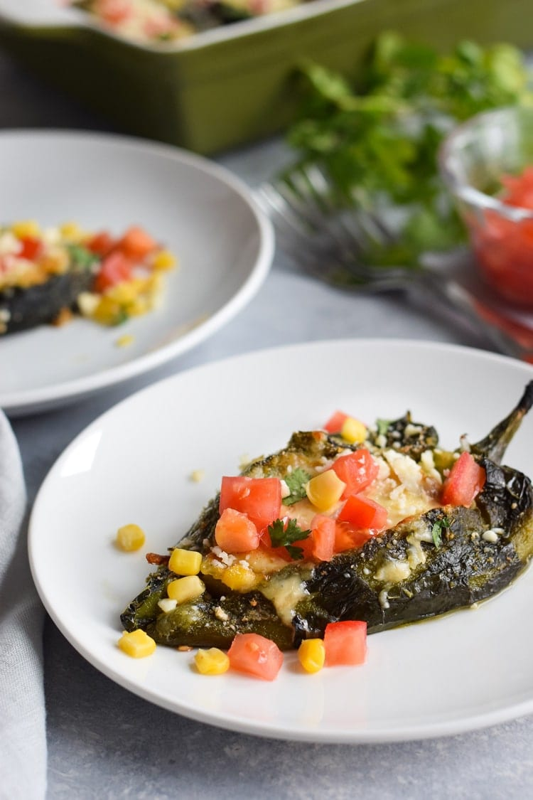 Baked chile rellenos topped with cilantro and tomatoes.