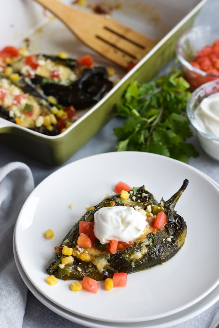 Baked chile relleno on a plate topped with sour cream.