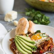 shakshuka on a plate with avocado slices and bread