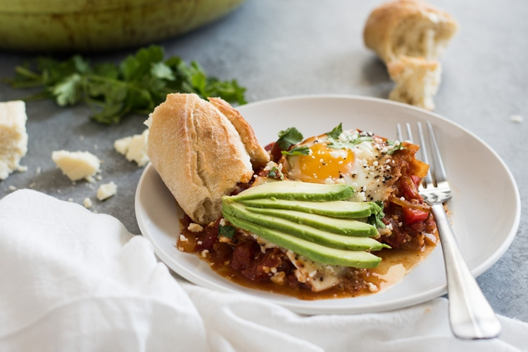Shakshuka on a white place with avocado slices and fresh crusty bread.