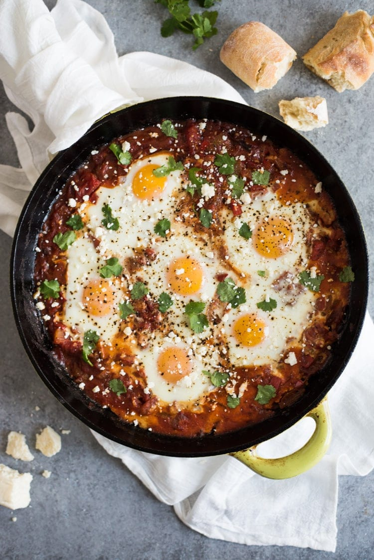 Shakshuka recipe in a cast iron skillet topped with cilantro and cotija cheese.