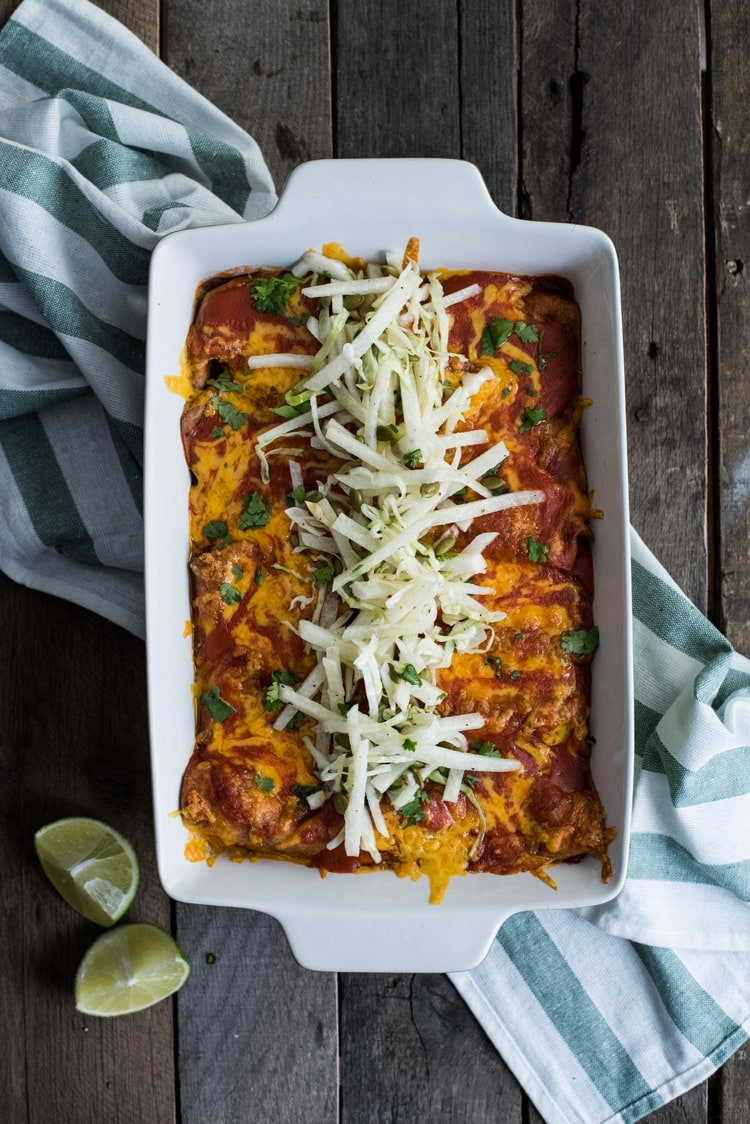 Covered in a red enchilada sauce, these Mexican Ground Beef Enchiladas with Lime Jicama Slaw are great for dinner and make tasty leftovers that everyone will be excited to eat!