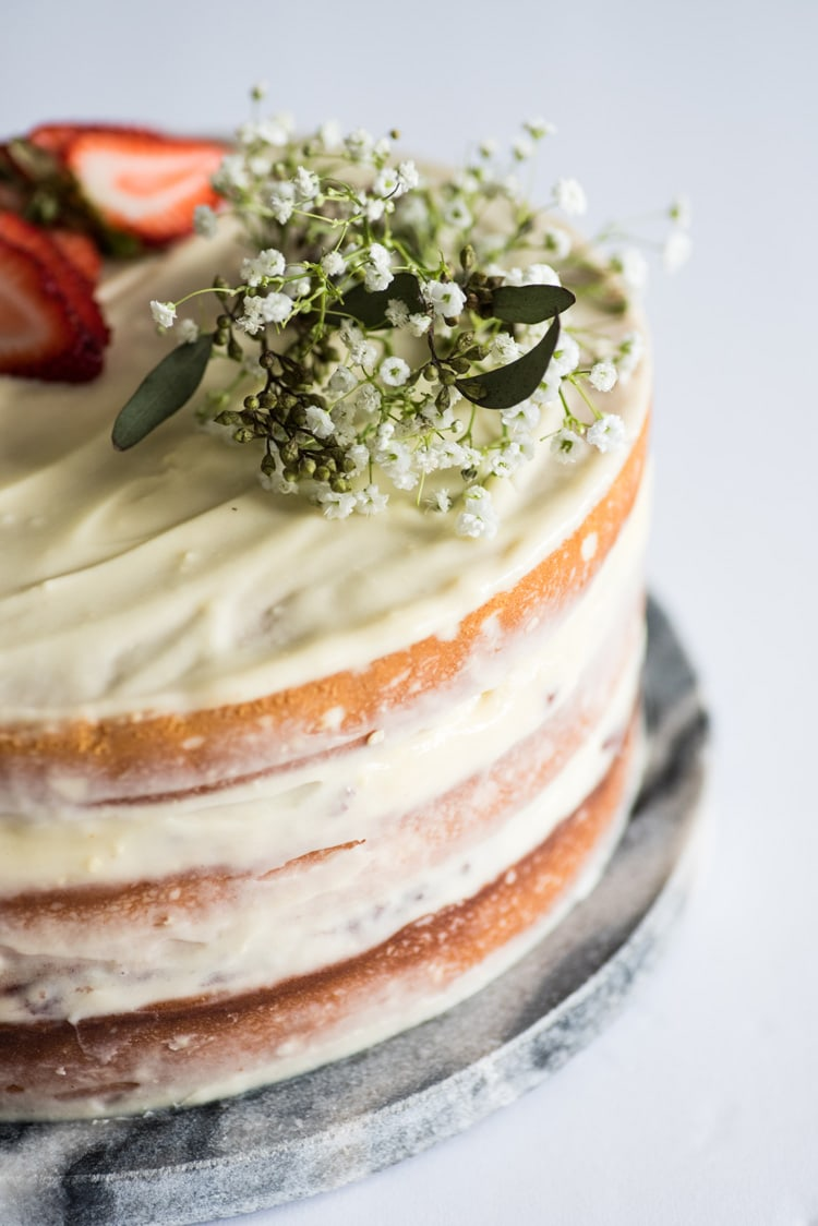 """This Homemade Yellow Cake with Vanilla Cream Cheese Frosting is a rich and buttery layered """"naked cake"""" perfect for any celebration!"""