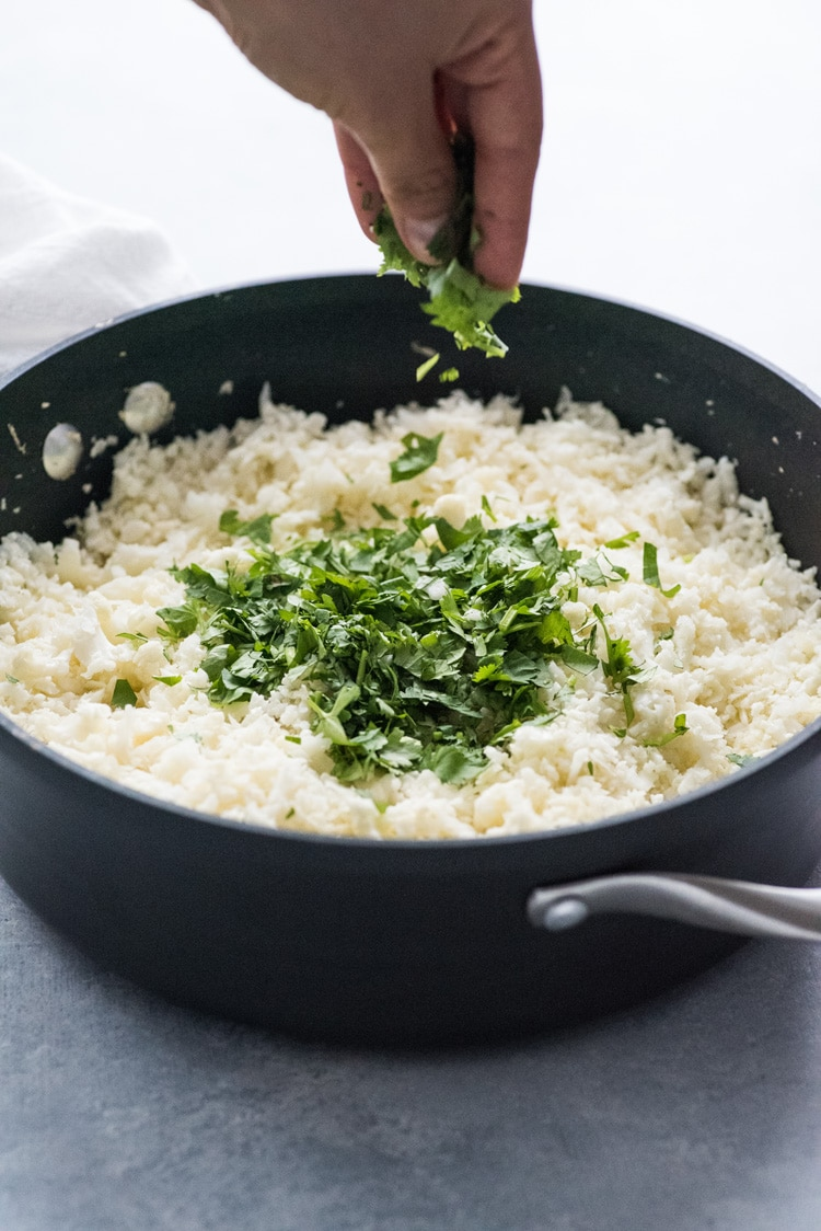 Hands dropping chopped cilantro onto mexican cauliflower rice in a pot