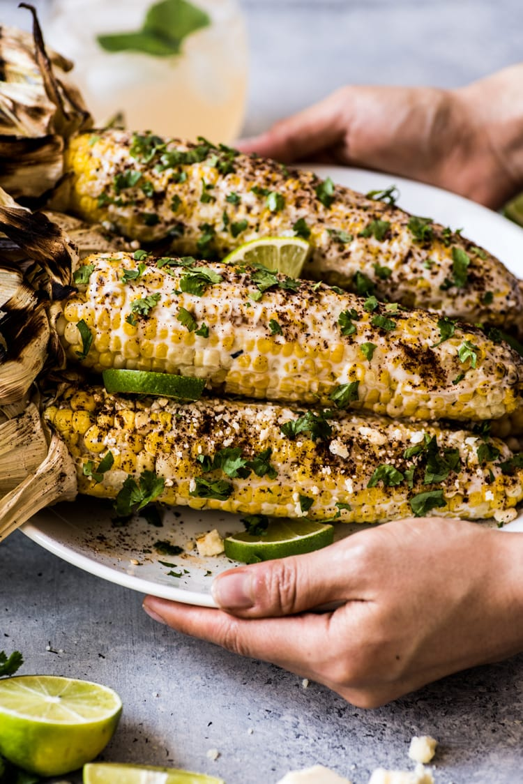 Mexican Corn on the cob covered in creamy mayo and topped with cilantro, lime juice, Cotija cheese and chili powder.