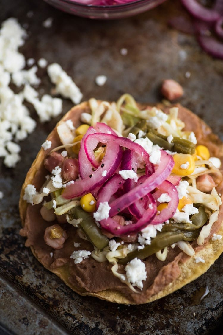 These Nopales Slaw Tostadas made with hominy and Mexican nopalitos (cactus leaves) are ready in only 35 minutes and are topped with homemade Easy Pickled Red Onions for a vegetarian and gluten free lunch.