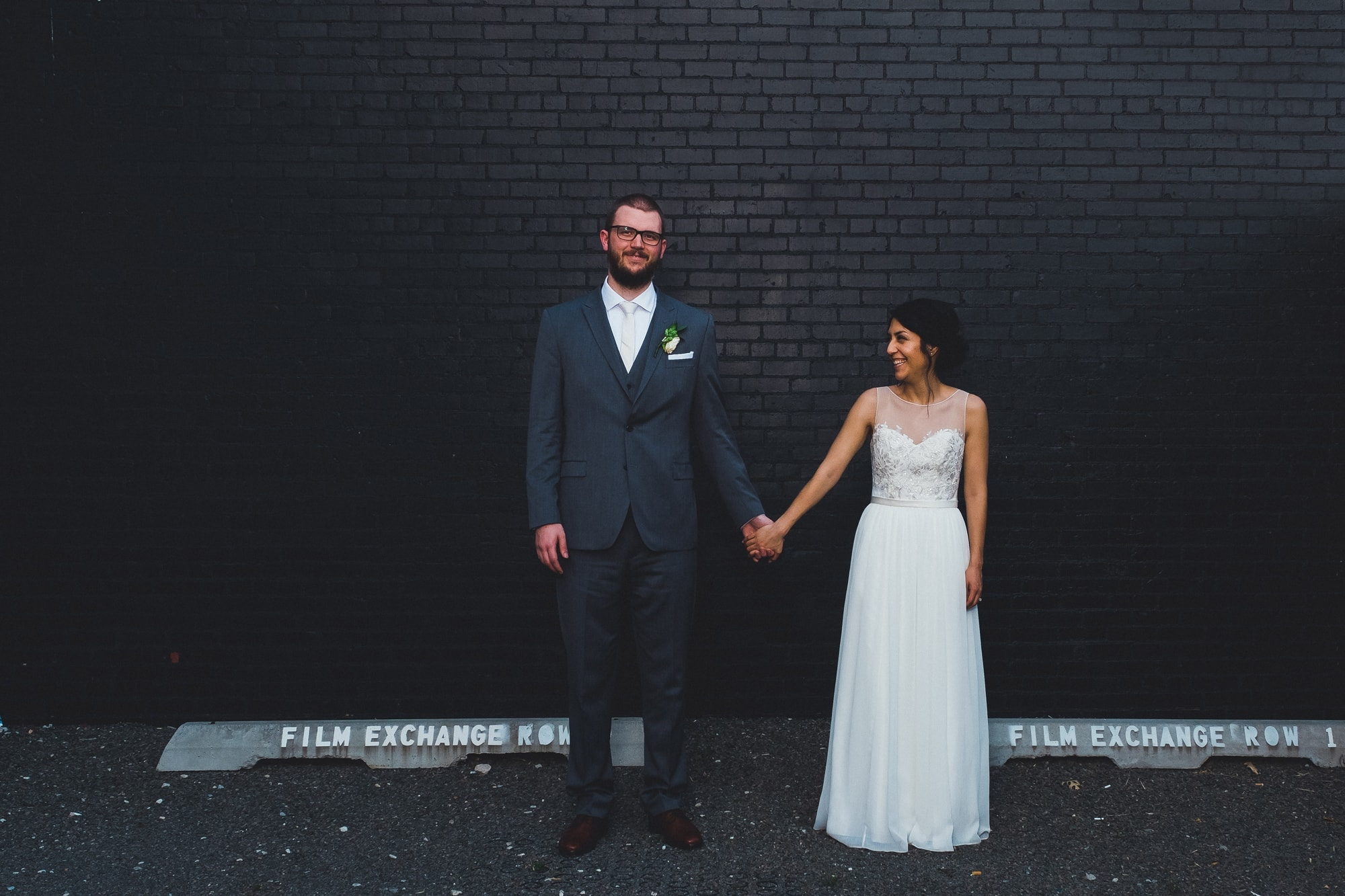 John Moore and Isabel Orozco Moore holding hands in Film Row in Oklahoma City on their wedding day. David's Bridal sheath dress and Men's Warehouse grey suit. // Photo by Leia Smethurst