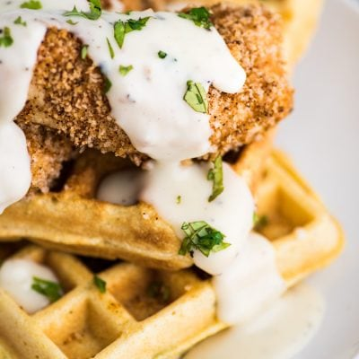 These savory Jalapeno Cornbread waffles are topped with crispy oven baked chicken tenders and white gravy for the ultimate brunch dish!