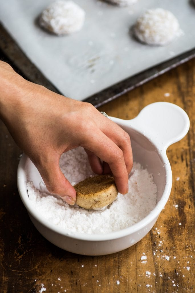 A mexican wedding cookie being dipped in powdered sugar.