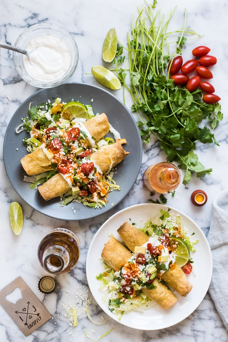 These baked Chicken Taquitos are stuffed with seasoned shredded chicken, cream cheese, diced green chiles, black beans and corn. Perfect for any weeknight meal! (freezer friendly, gluten free)