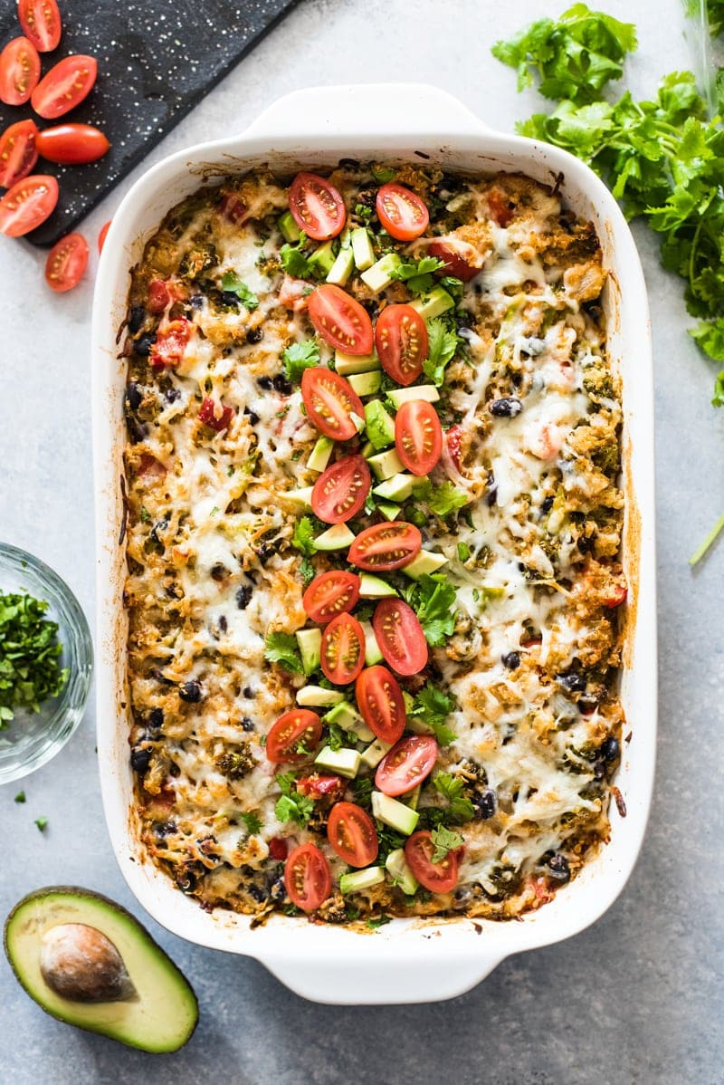 A Quinoa Enchilada Bake topped with tomatoes, cilantro and avocados.