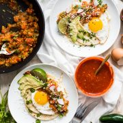 This Easy Huevos Rancheros recipe features crispy corn tortillas topped with fried eggs covered in a spicy tomato jalapeno salsa. (vegetarian, gluten free)