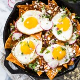 Red chilaquiles topped with sunny side up eggs in a black cast iron skillet.