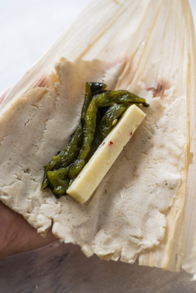 Filling tamales with poblano peppers and cheese (tamales de rajas y queso)