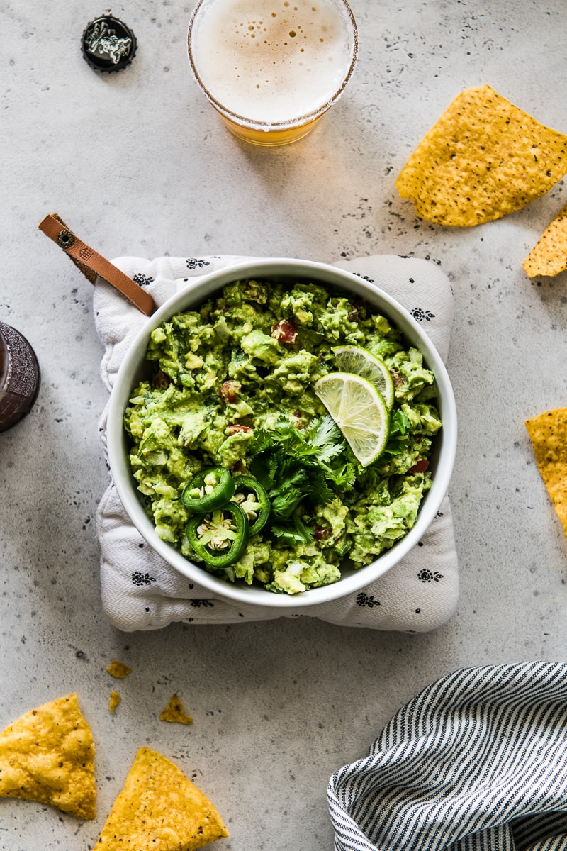 Bowl of guacamole with tortilla chips next to it.