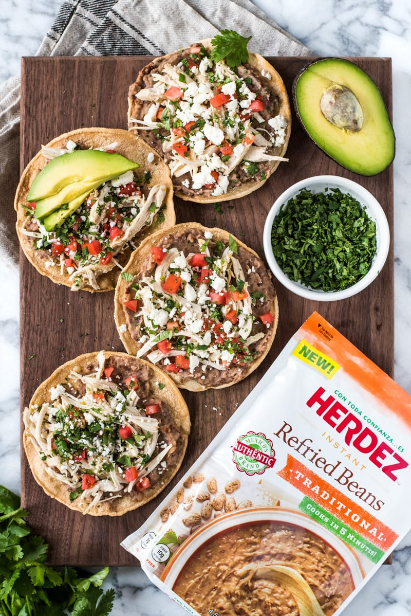 These crispy and crunchy Slow Cooker Salsa Verde Chicken Tostadasare topped with a layer of delicious refried beans, salsa verde chicken, tomatoes, cilantro, queso fresco and avocados.
