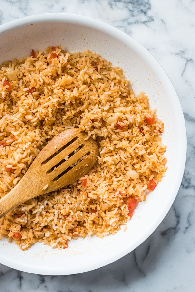 Authentic Mexican rice in a skillet with tomatoes and onions