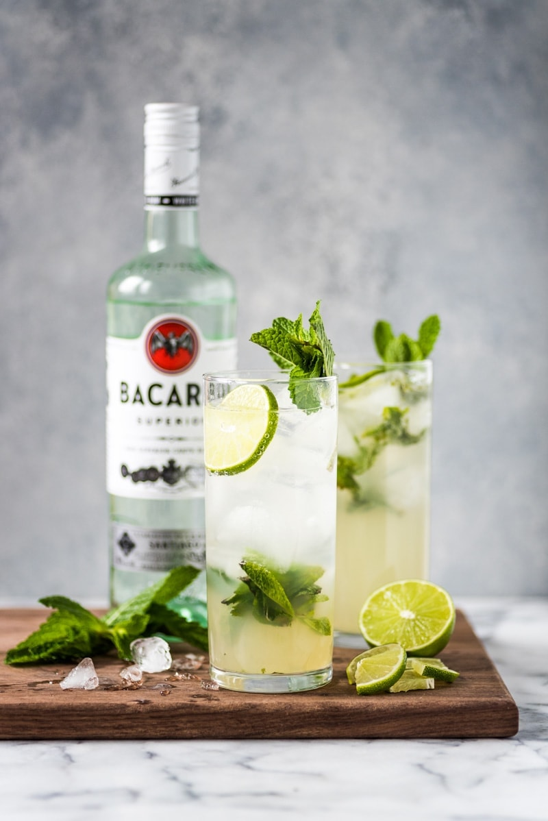 Two glasses of mojitos topped with fresh mint leaves and limes.