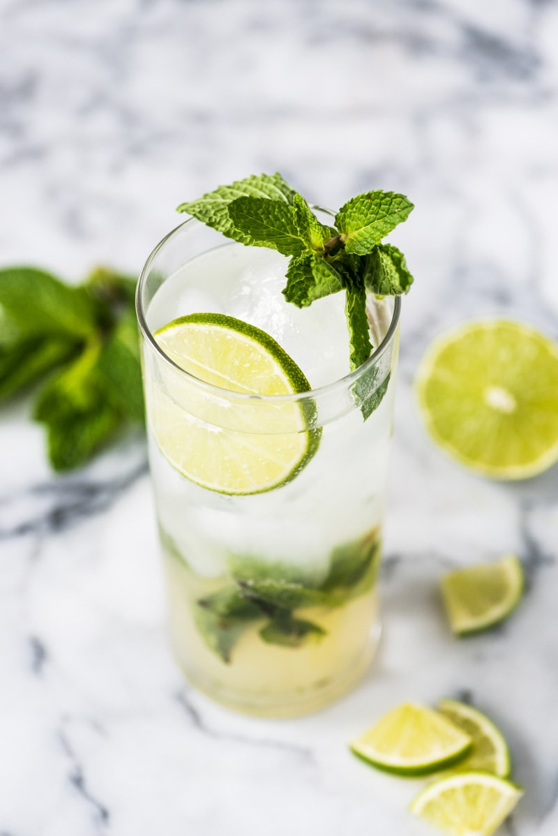 A mojito cocktail in a tall clear glass topped with mint leaves and limes.