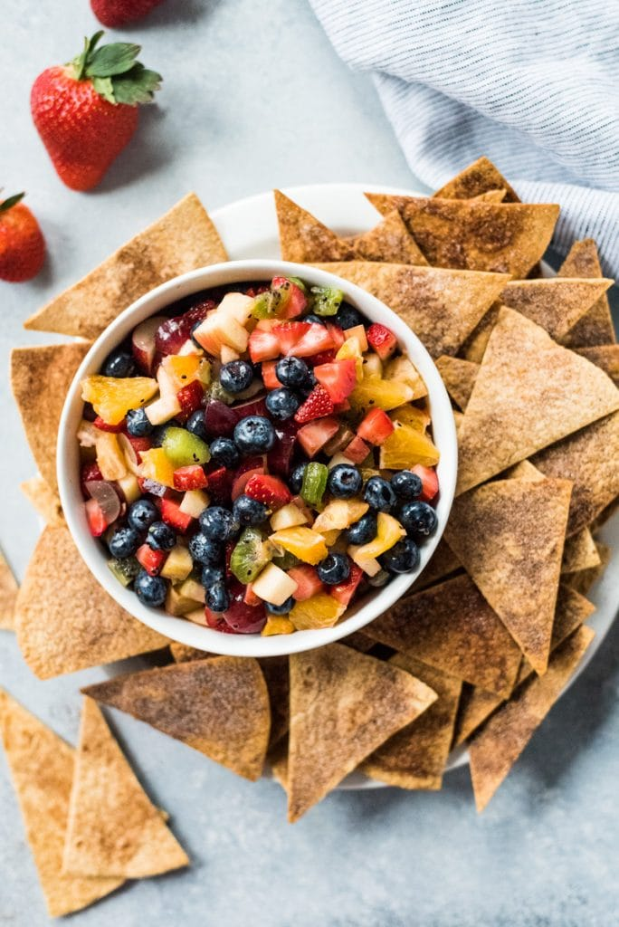 This Fruit Salsa with Cinnamon Chips recipe is made with 6 different types of fruit and is served with baked cinnamon sugar tortilla chips for a fun appetizer or healthy dessert!