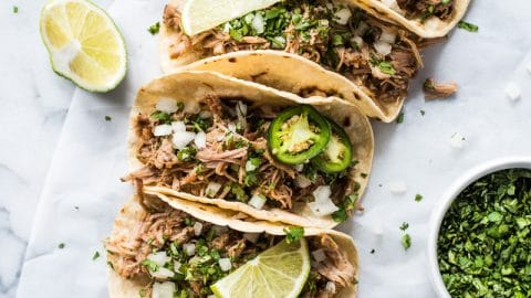 Juicy pork carnitas in warm corn tortillas topped with cilantro, onions and limes.