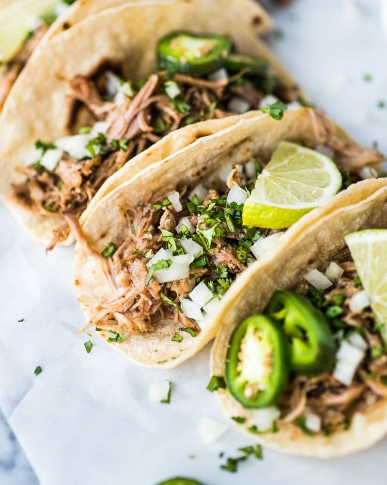 Carnitas tacos topped with chopped cilantro, diced onions and jalapenos.