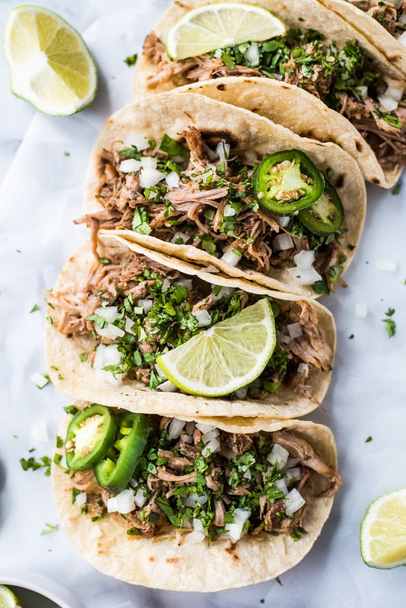 Mexican carnitas recipe in corn tortillas with onions, cilantro, limes and jalapenos.