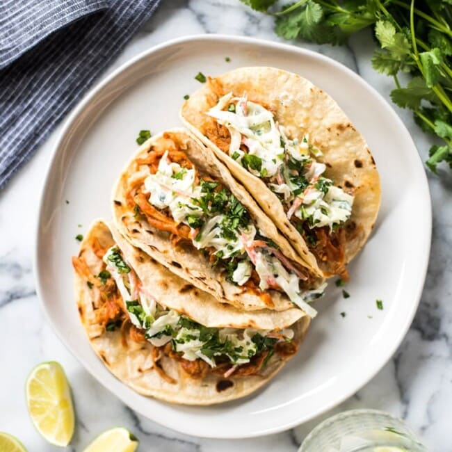 These Slow Cooker BBQ Pulled Pork Tacos served with a cilantro lime coleslaw are easy to make and perfect for healthy weeknight meals! The recipe is gluten free and freezer-friendly.