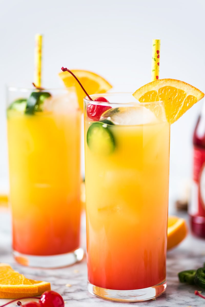 A Tequila Sunrise made with orange juice, tequila and grenadine. Garnished with an orange slice, maraschino cherries and jalapeno slices.