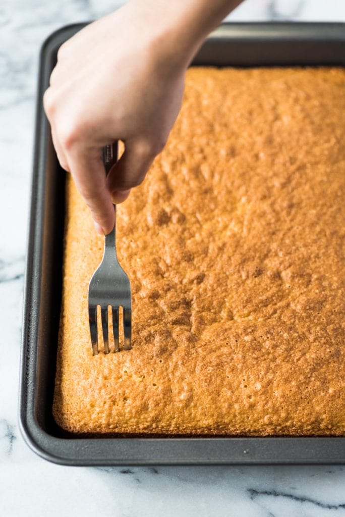 Poking tres leches cake with a fork.