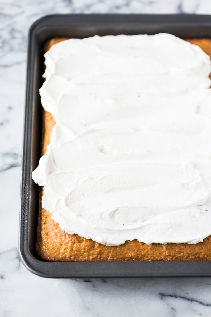 Whipped cream topping spread over a tres leches cake in a pan.