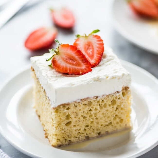 A slice of tres leches cake topped with fresh strawberries