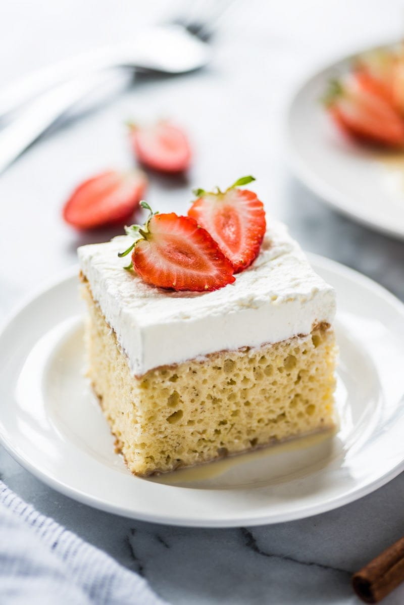 A square slice of tres leches cake topped with whipped cream and strawberries on a white plate.