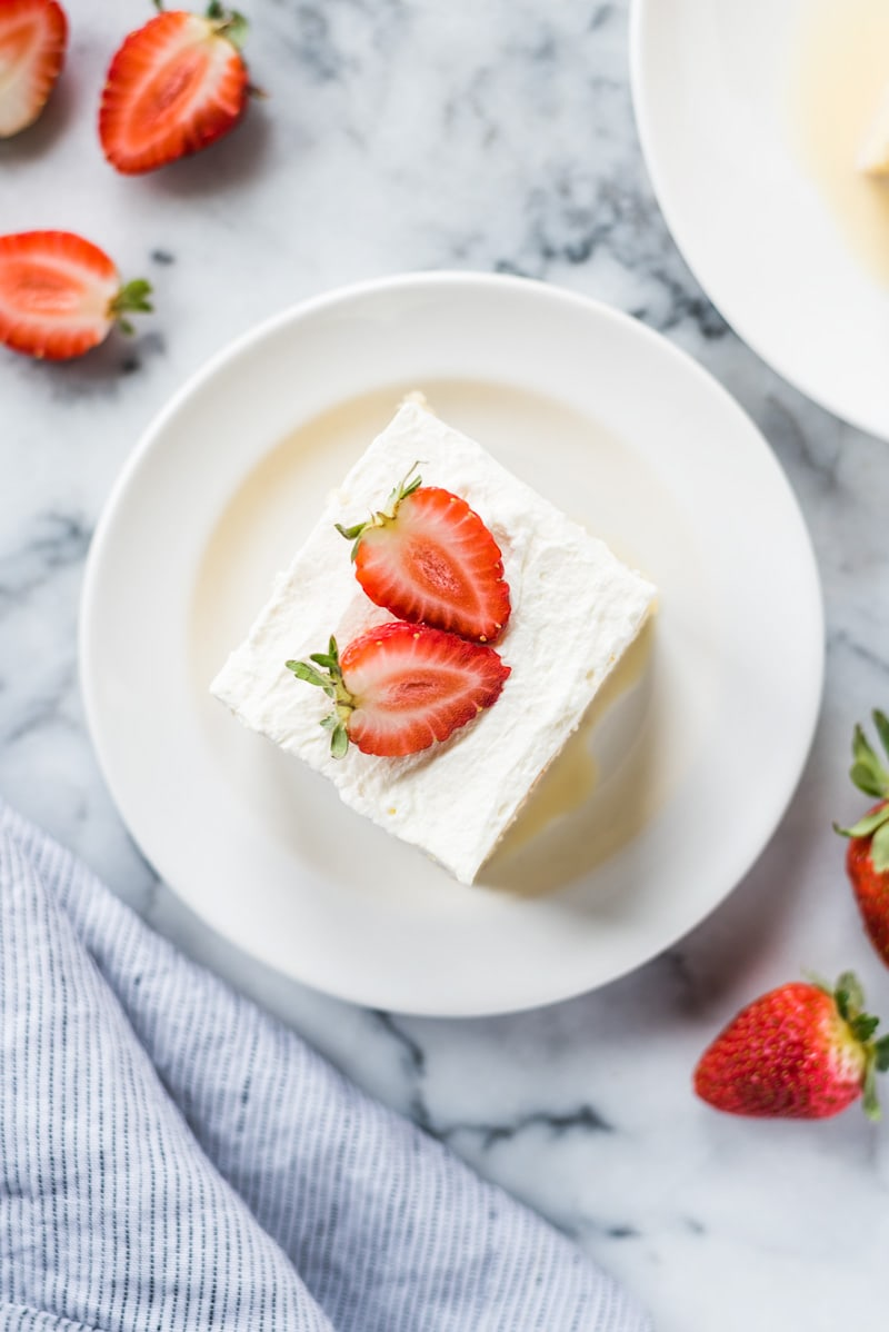 A slice of tres leches cake topped with whipped cream on a white plate with strawberries around it.