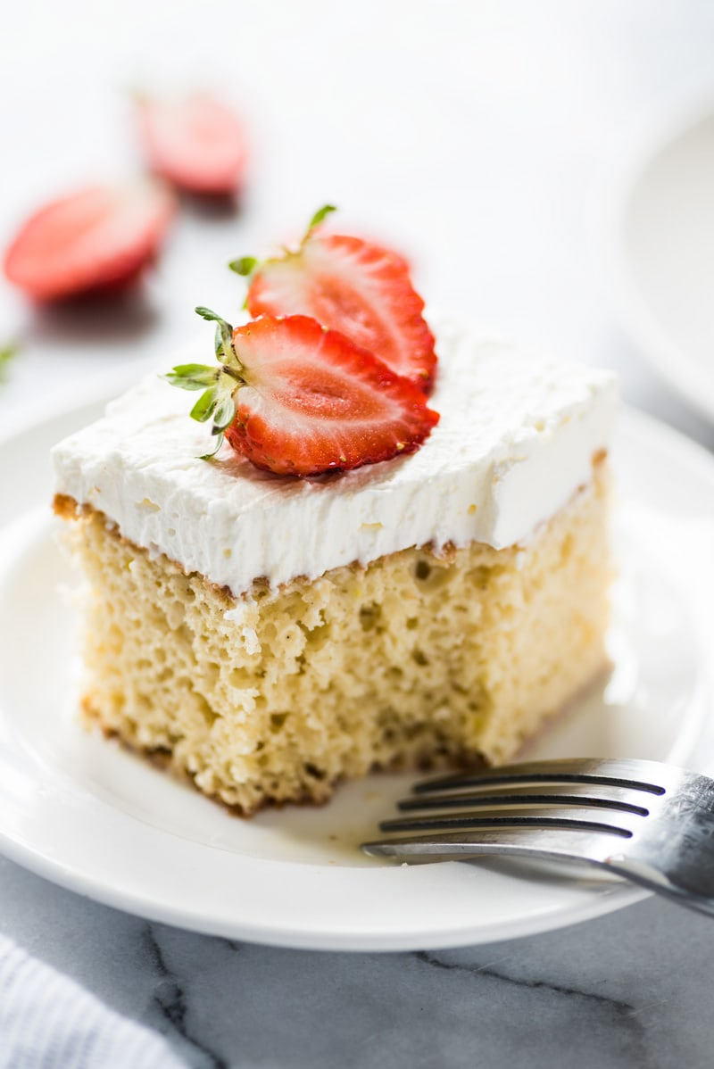 A slice of tres leches cake topped with whipped cream and fresh cut strawberries on a white plate.