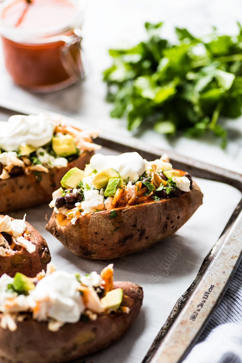 These Chicken Enchilada Stuffed Sweet Potatoes are an easy to make Mexican inspired dinner recipe stuffed with shredded chicken, red enchilada sauce and all your favorite toppings! (gluten free)