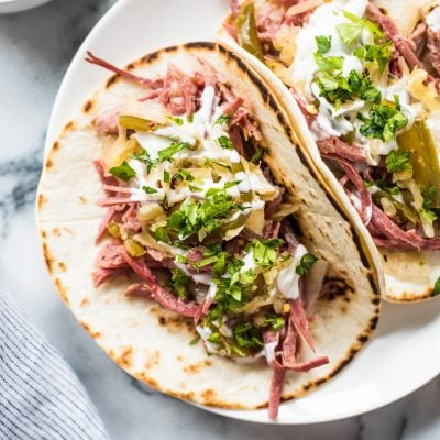 Slow cooker corned beef tacos in a flour tortilla topped with sauerkraut and sour cream.