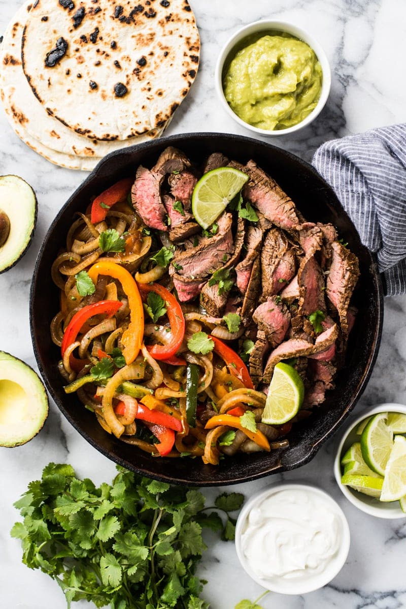 Cooked Steak Fajitas with Onions and Peppers in a Black Cast Iron Pan