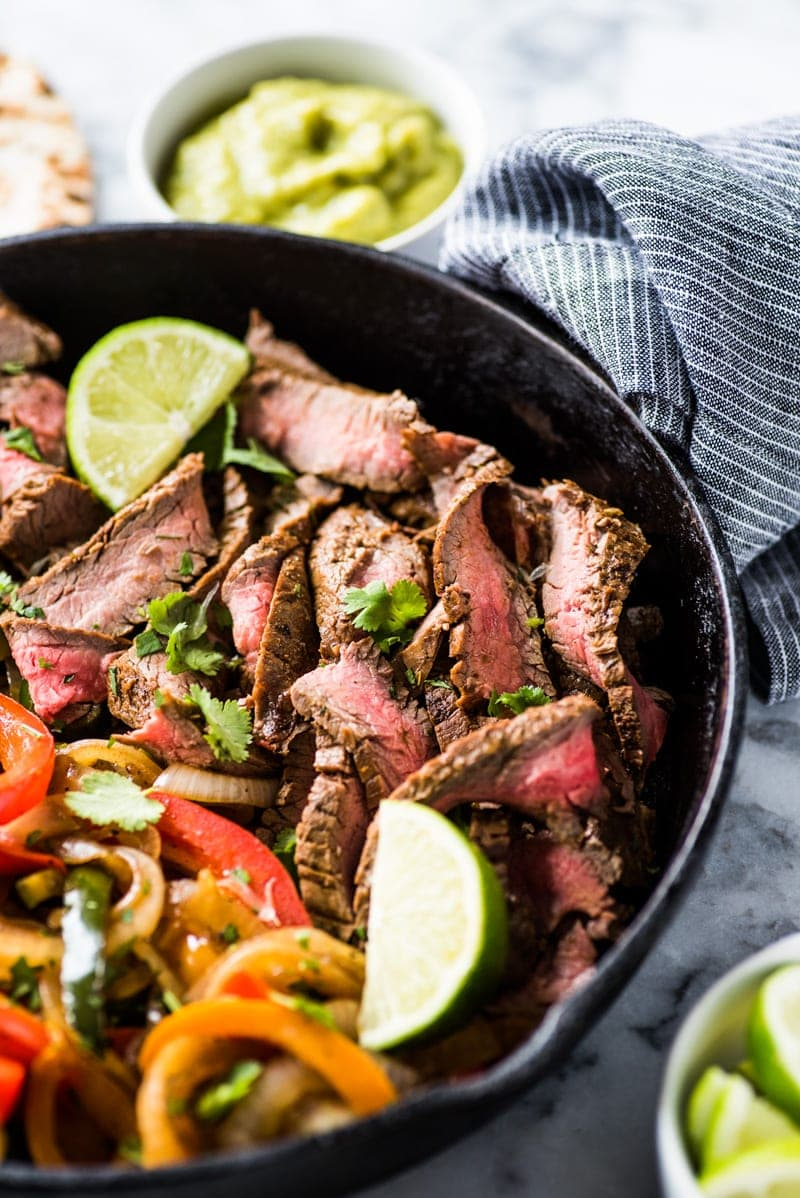This Steak Fajita Marinade is made with olive oil, orange juice, lime juice, garlic and flavorful herbs and spices that result in tender and juicy fajitas!